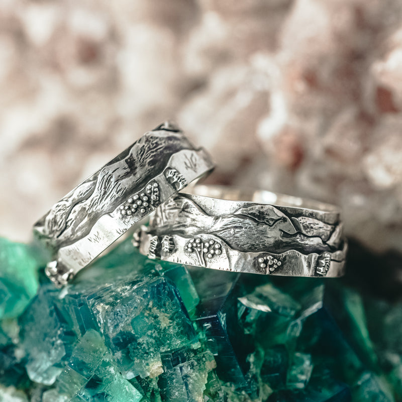 The White Mountains of New Hampshire mountain line on a sterling silver ring. Both rings are shown on a piece of dark green mineral stone.