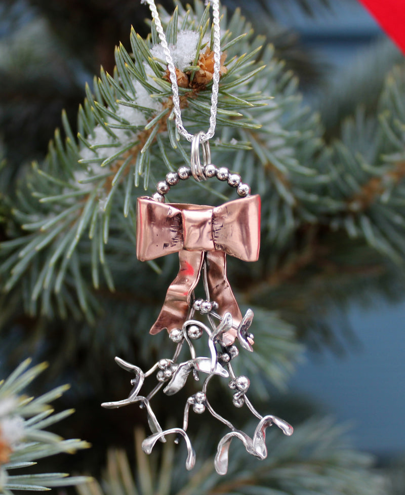 A copper bow holds onto several sprigs of sterling silver mistletoe. The pendant has a loop on the top to hold it onto a necklace. The necklace is shown in front of a green pine tree.