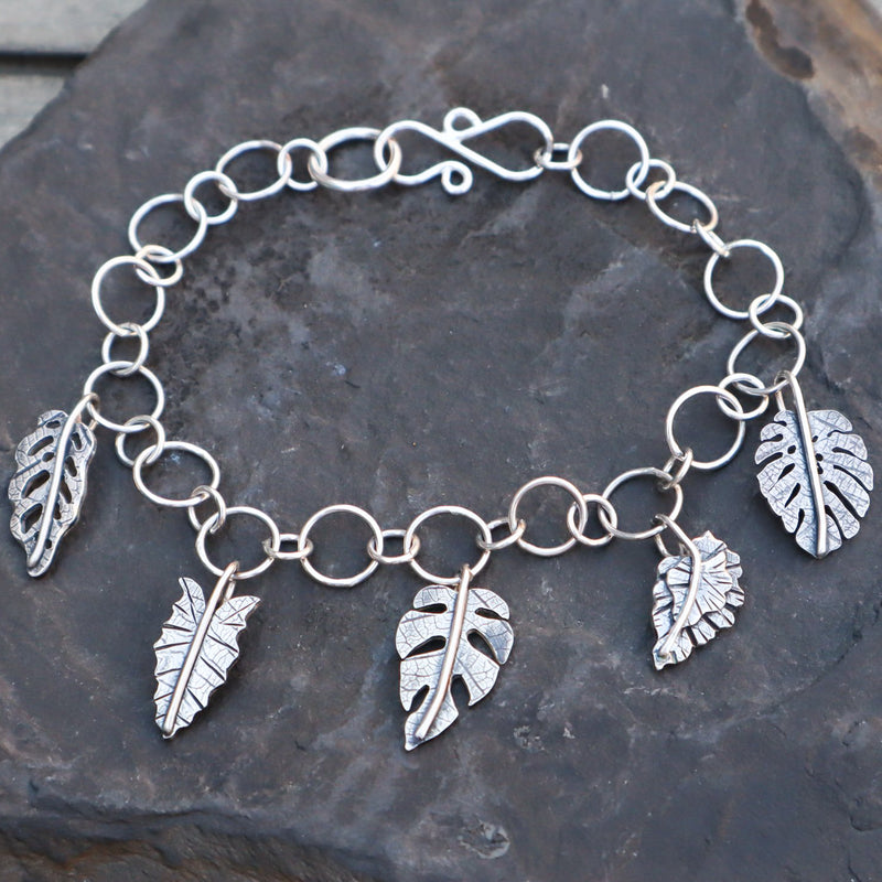 A handmade sterling silver bracelet with 5 silver houseplant leaves. It features a monstera adansonii, african mask, rhaphidophora tetrasperma, an angel wing begonia, and a monstera deliciosa. The bracelet is shown on a dark slate stone.