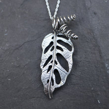 Load image into Gallery viewer, Handmade sterling silver monstera adansonii necklace shown in a black rock with twisted stems