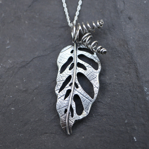 Handmade sterling silver monstera adansonii necklace shown on a black rock with twisted stems.