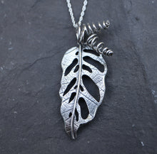 Load image into Gallery viewer, A handmade sterling silver monstera adansonii necklace made by The Striped Cat Metalworks. The necklace is pictured on a dark grey piece of slate.