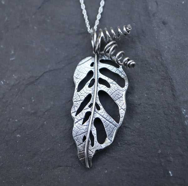 A handmade sterling silver monstera adansonii necklace made by The Striped Cat Metalworks. The necklace is pictured on a dark grey piece of slate.
