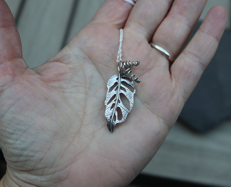 A monstera adansonii silver pendant being shown in a hand for size.