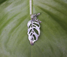 Load image into Gallery viewer, a handmade sterling silver monstera adansonii pendant on a necklace shown in front of a green leaf