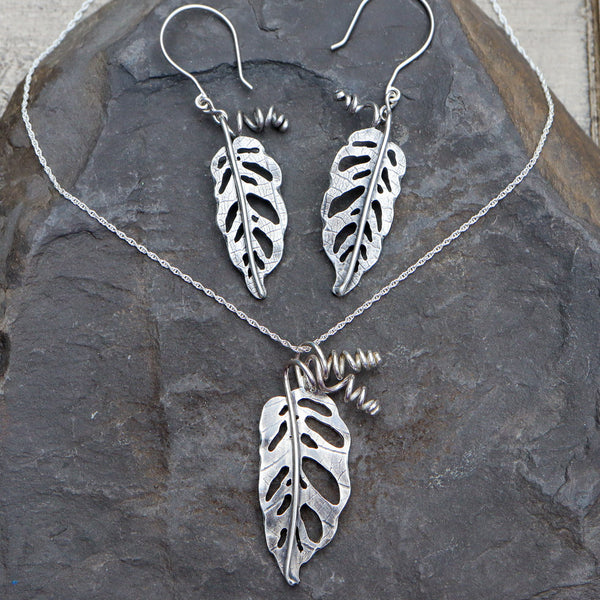 Monstera adansonii earrings and a necklace set that come together. The necklace leaf is about 1.5 inches tall and the earrings are a little smaller. They are shown on a dark grey piece of slate.