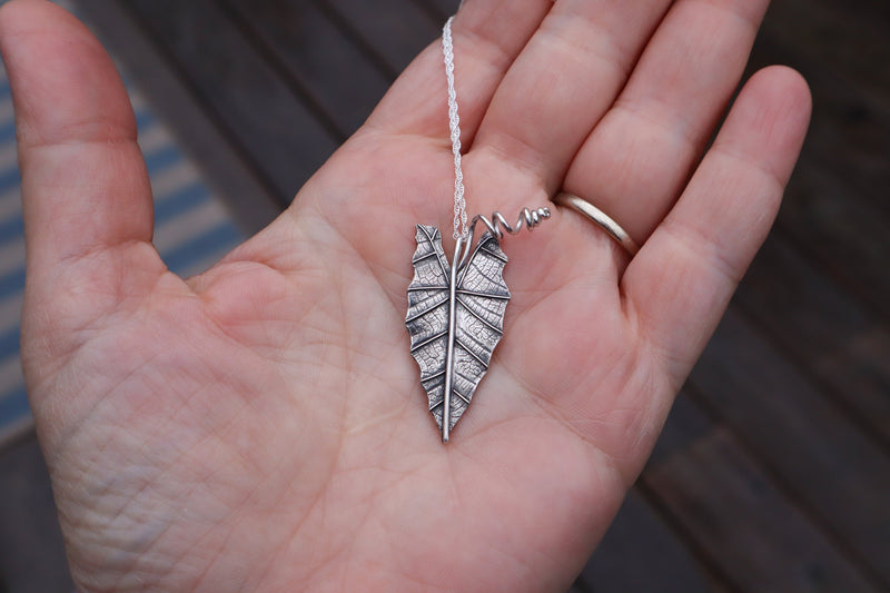 photo is of a hand holding a sterling silver african mask leaf plant necklace made by The Striped Cat Metalworks in Massachusetts.
