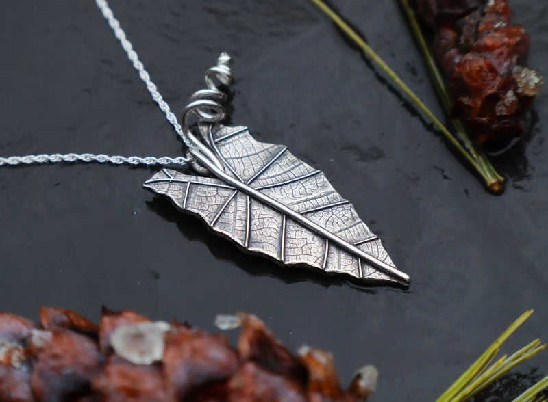 A handmade sterling silver alocasia african mask leaf made into a necklace shown from the side view. It is about 1.5 inches tall and is pictured on a dark slate stone with pinecones and greenery around it.
