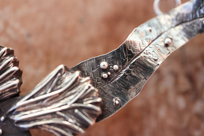 A close up of the silver detailing on a part of the anglerfish necklace.