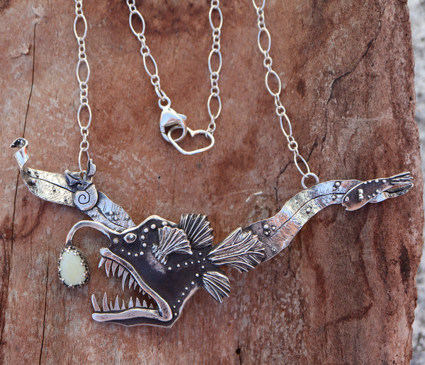 A handmade silver anglerfish pendant with a male fish on the right side and a butterfly snail on the left. The necklace has a heart shaped clasp and is shown on a piece of light brown wood.
