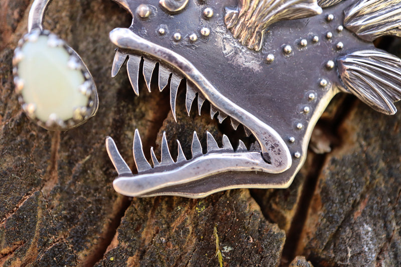 A close up photo of the female anglerfishes sharp silver teeth.