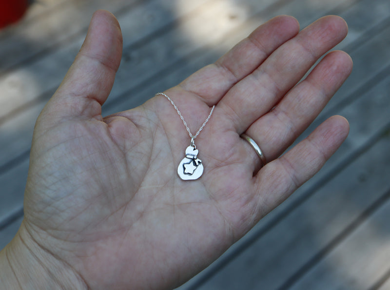 A hand holding a handmade sterling silver Animal Crossing bells bag jewelry pendant.