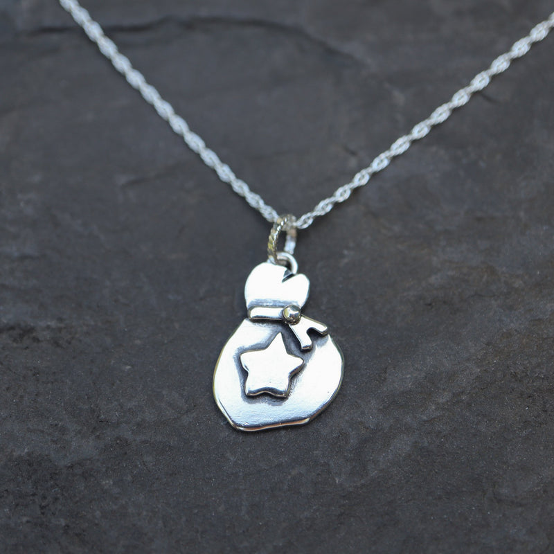 Animal Crossing sterling silver bells bag necklace shown on a dark grey slate background.