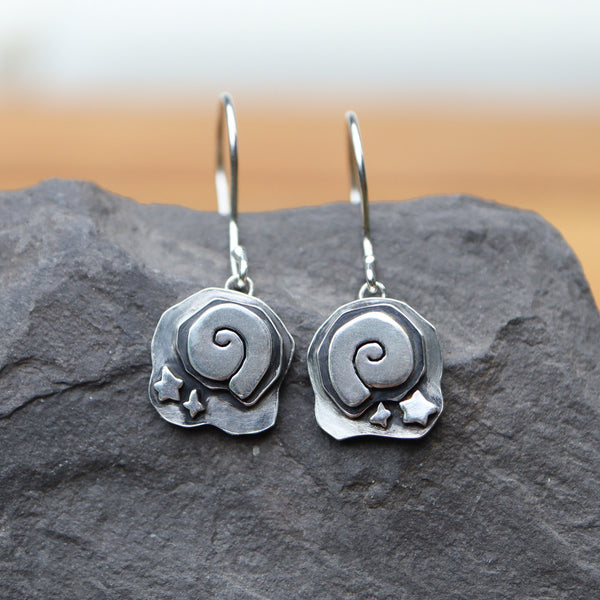 Animal Crossing New Horizon sterling silver fossil earrings. They are about 1.25 inches long and about .5 inches wide. The dangle earrings with french wire hooks are shown on a dark grey piece of slate.