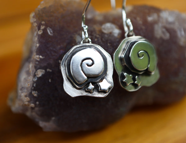 Animal Crossing New Horizon sterling silver fossil earrings. They are about 1.25 inches long and about .5 inches wide. The dangle earrings with french wire hooks are shown on a dark purple pieces of gemstone with one of them mainly in focus.