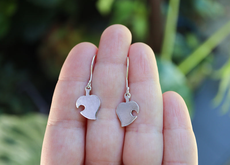 A hand holding stelring silver handmade nook leaf earrings from the game Animal Crossing. They are about .75 inches tall.