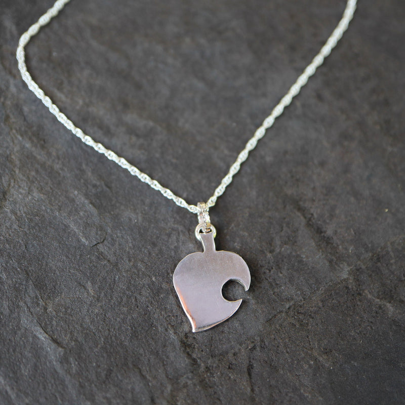 A sterling silver Nook leaf necklace that is about .75 inches tall and shown on a dark grey piece of slate.