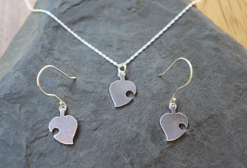 A jewelry set of a handmade pair of earrings and a Nook leaf necklace. They are each about .75 inches tall and shown on a dark grey piece of slate.