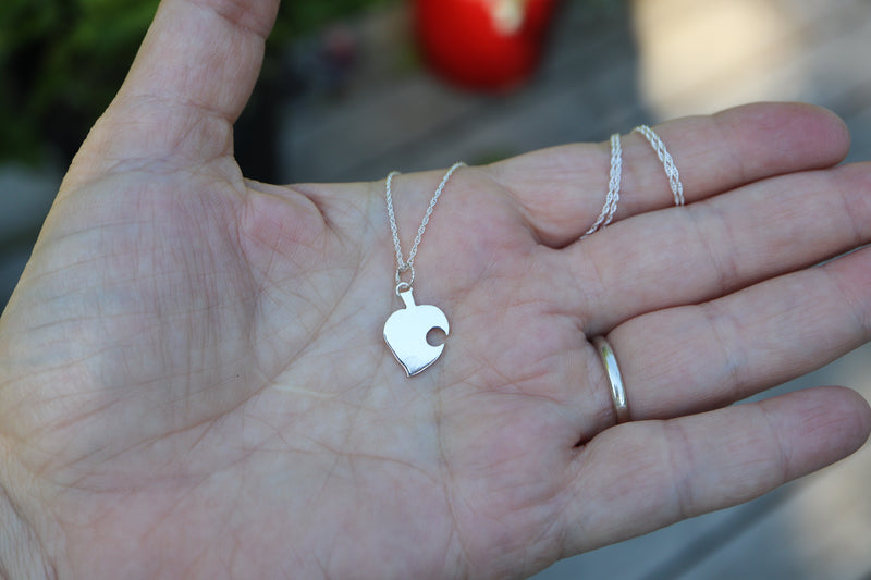 A hand is holding a Nook leaf pendant on a necklace to show size reference..