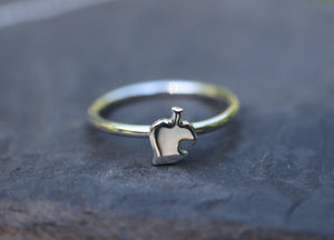 A dainty Nook leaf ring shown on a round circular band and on top of a dark grey piece of slate.