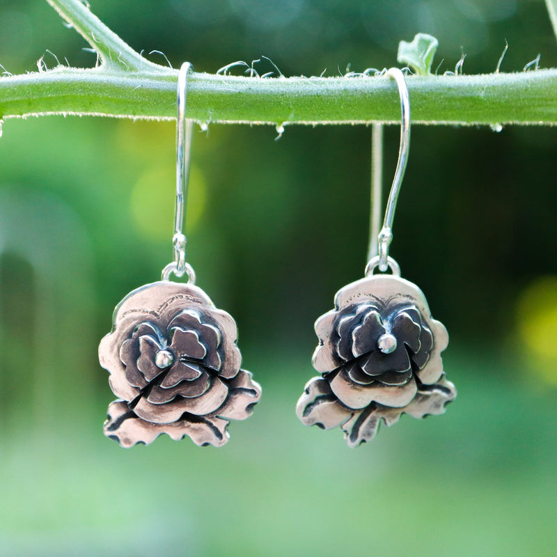 Sterling silver pansy earrings that represent pansies from the video game Animal Crossing New Horizons. They are made entirely from sterling silver with darkened centers and dangle from silver earring wires. The earrings are about .75 inches tall.