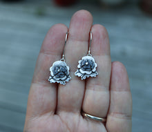 Load image into Gallery viewer, A hand is shown holding apair of handmade sterling silver pansy earrings that represent sweet pansies in the game of Animal Crossing New Horizons. They are about .75 inches tall with darkened centers.