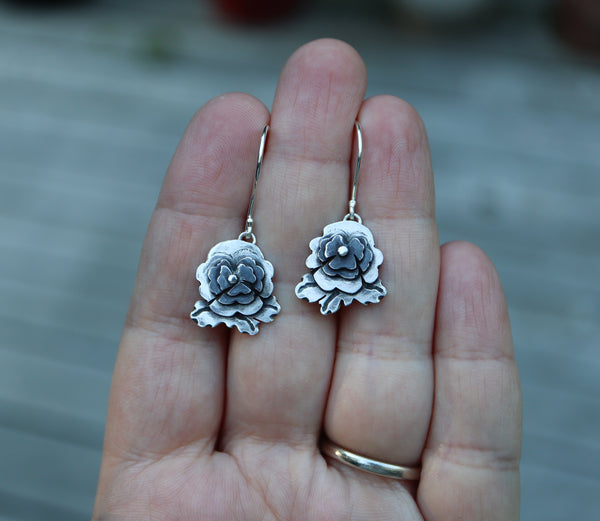 A hand is shown holding apair of handmade sterling silver pansy earrings that represent sweet pansies in the game of Animal Crossing New Horizons. They are about .75 inches tall with darkened centers.