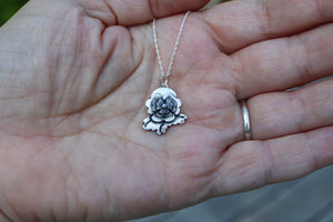 A hand is holding a .75 inch tall pansy necklace from Animal Crossing New Horizons. It is made from sterling silver and about .75 inches tall.