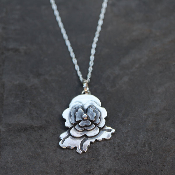 An Animal Crossing pansy pendant that was handmade from multiple layers of sterling silver and given a darkened center. The flower is about .75 inches tall and is on a silver necklace.