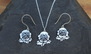 A jewelry set of a pansy necklace with a pair of dangle pansy earrings is shown on a piece of dark grey slate. The necklace is on a silver chain and the earrings are on French ear wire hooks.