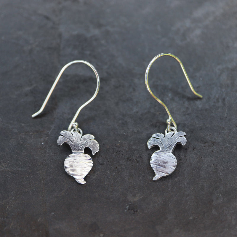 Little sterling silver handmade turnip earrings from Animal Crossing. They are shown on a piece of dark grey slate and are about .75 inches tall.