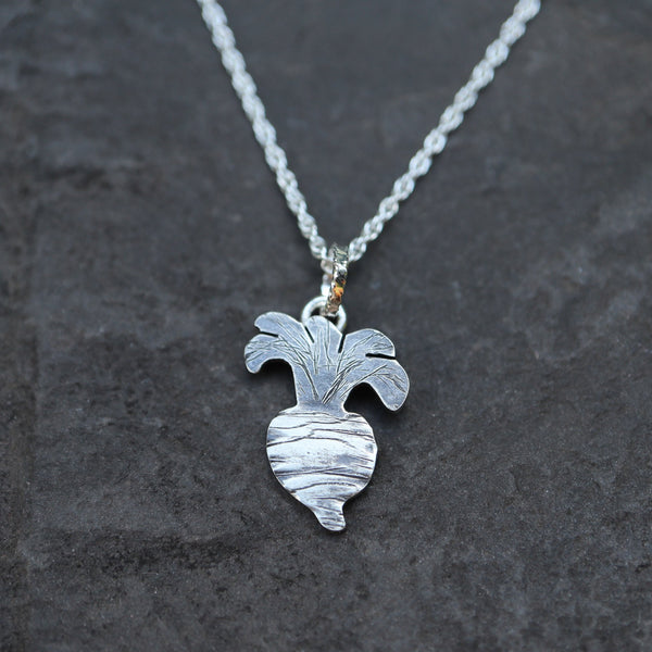 A handmade sterling silver turnip pendant from Animal Crossing New Horizons shown in a pieces of dark grey slate.