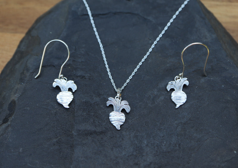 A pair if dangly turnip earrings and a turnip necklace are shown on a dark grey piece of slate. The earrings and the pendant itself is about .75 inches tall.