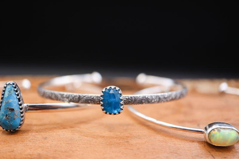 A pretty light blue faceted apatite stone with a swirly silver band.