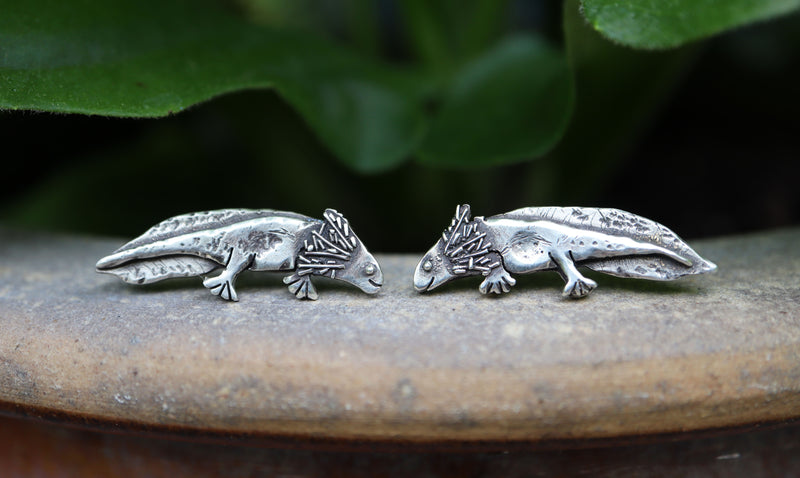 Handmade sterling silver axolotl earring studs are about 1/2 inch long and are shown on top of a light brown stone flower pot with some green leaves behind them.