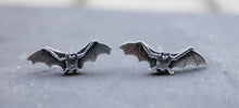 Load image into Gallery viewer, handmade sterling silver bat stud earrings show on a dark rock