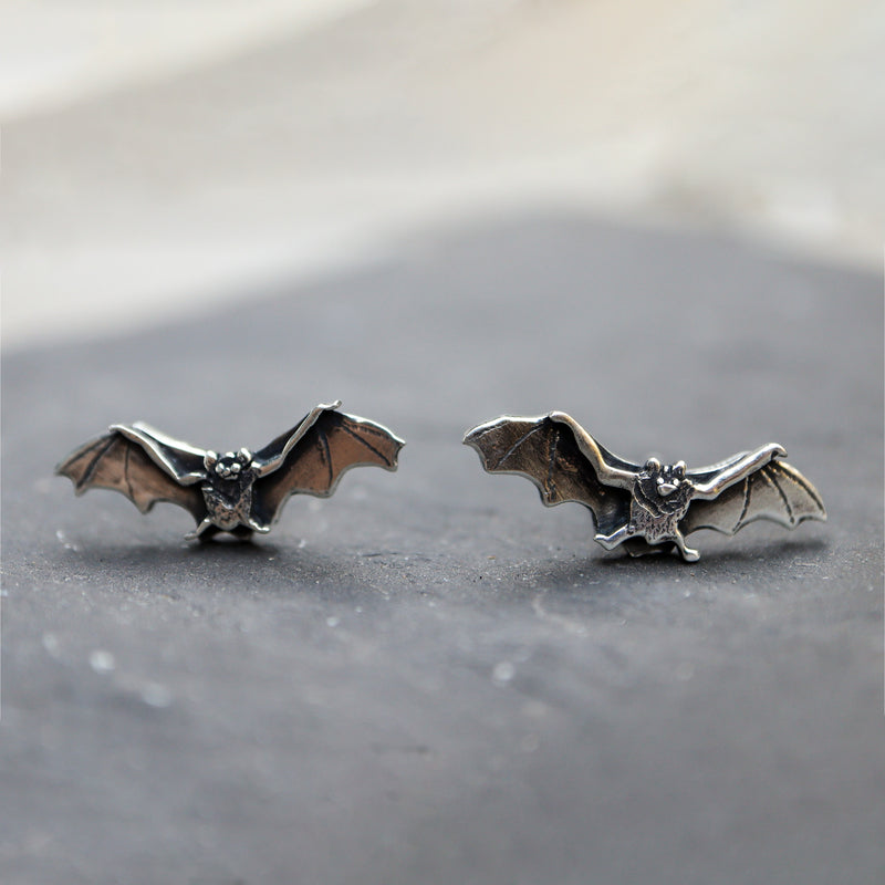 Baby bat earrings made from sterling silver and one of a kind. They are about 3/4 inch wide and shown with their arms outstretched in flight.