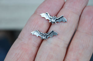 A pair of sterling silver baby bat earrings shown in a hand for size refrence