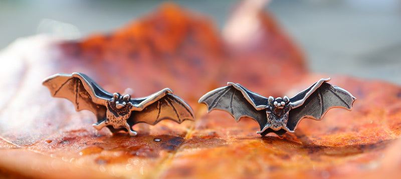 Sterling silver tiny bat stud earrings are shown on a bright orange fall leaf.