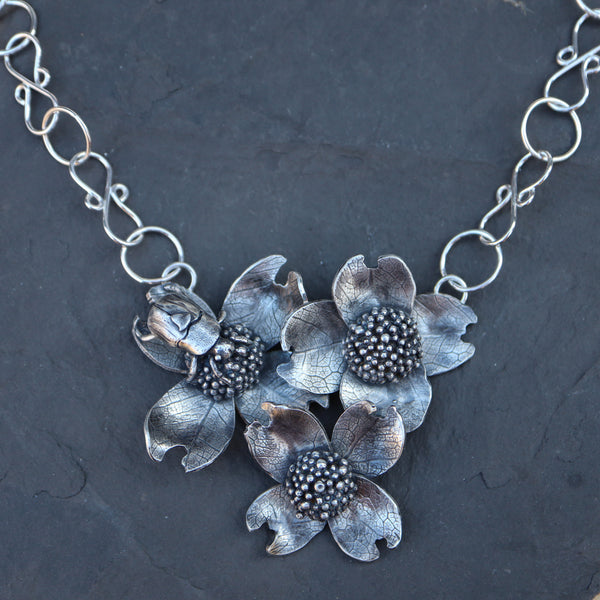 A handmade sterling silver dogwood flower and beetle necklace shown on top of a dark grey piece of slate.