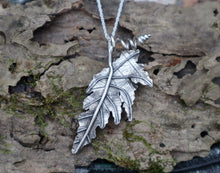 Load image into Gallery viewer, A sterling silver angel wing begonia leaf necklace shown on a piece of tree bark made by The Striped Cat Metalworks
