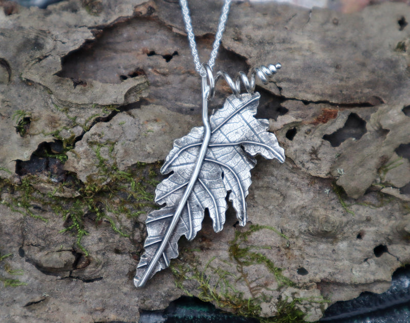 A sterling silver angel wing begonia leaf necklace shown on a piece of tree bark made by The Striped Cat Metalworks