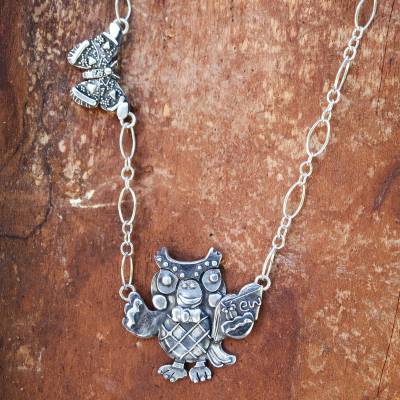 "Animal Crossing Blathers necklace with an atlas moth to the left of the necklace. Blathers is holding a little book with a tiny butterfly on it and the word ""ew"" next to it. This necklace is made from sterling silver and shown on a dark reddish brown piece of wood."