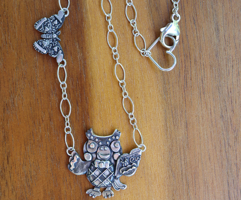 A sterling silver Blathers necklace with a 1 inch wide silver atlas moth within the necklace chain. There is a heart clasp at the end.