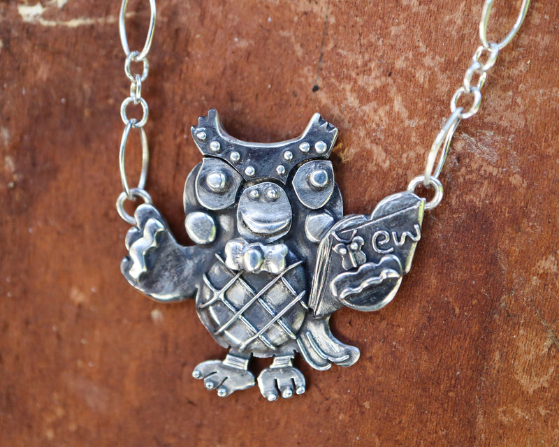 "A handmade sterling silver Blathers necklace from the video game Animal Crossing. He is holding a tiny silver book with a little butterfly on it and the word ""ew"" because he dislikes bugs. It is shown on a piece of reddish brown piece of wood."