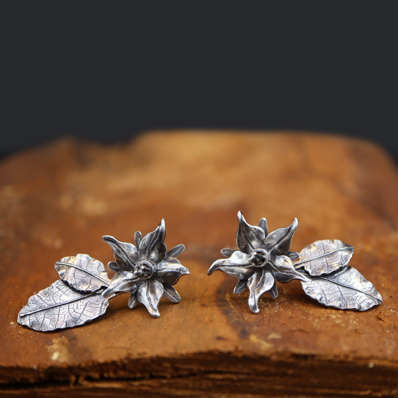 A pair of hand fabricated sterling silver borage flower earrings. There are a pair of little leaves to are also a part of the earrings. They are shown on a piece of dark brown wood.