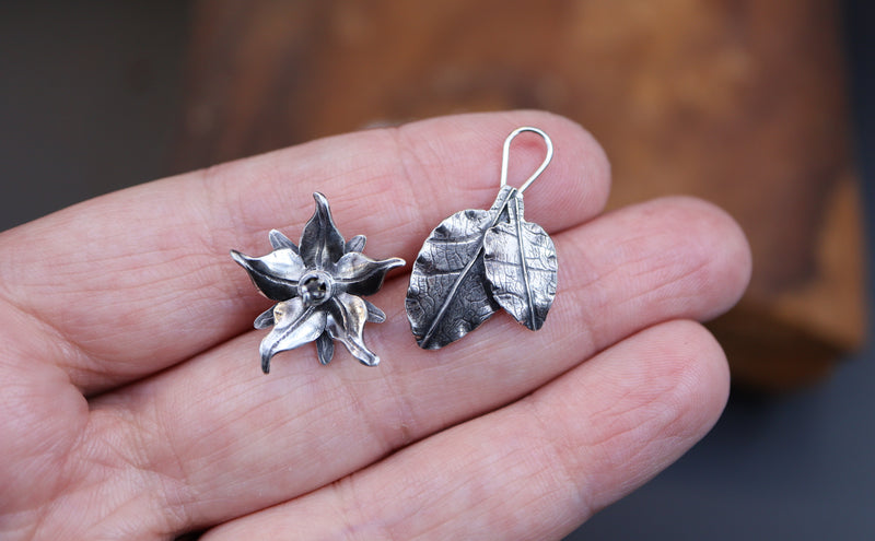 This shows that the earrings are made in two pieces. One piece is the flower with the post that is the earring, and the two leaves are one piece that loop onto the earring post.