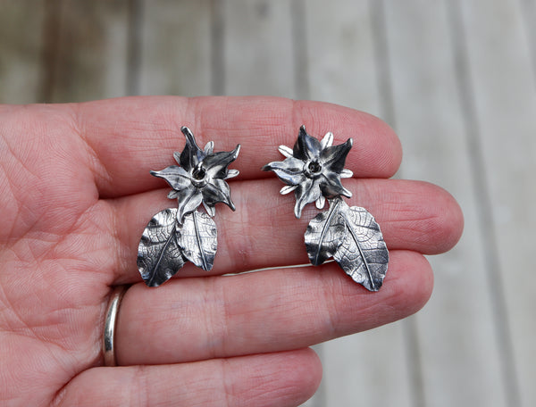 A hand is shown holding a pair of handmade silver borage flower earrings. The earrings are about 1 inch tall with the leaves below them making them a total of about 1.5 inches long.