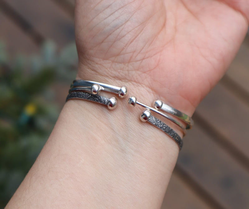 The backs of the three bracelets feature round silver calls at the end of each bracelet end.