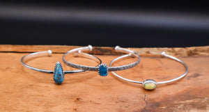 A set of three stacking bracelets with an apatite stone, an opal, and a turquoise.